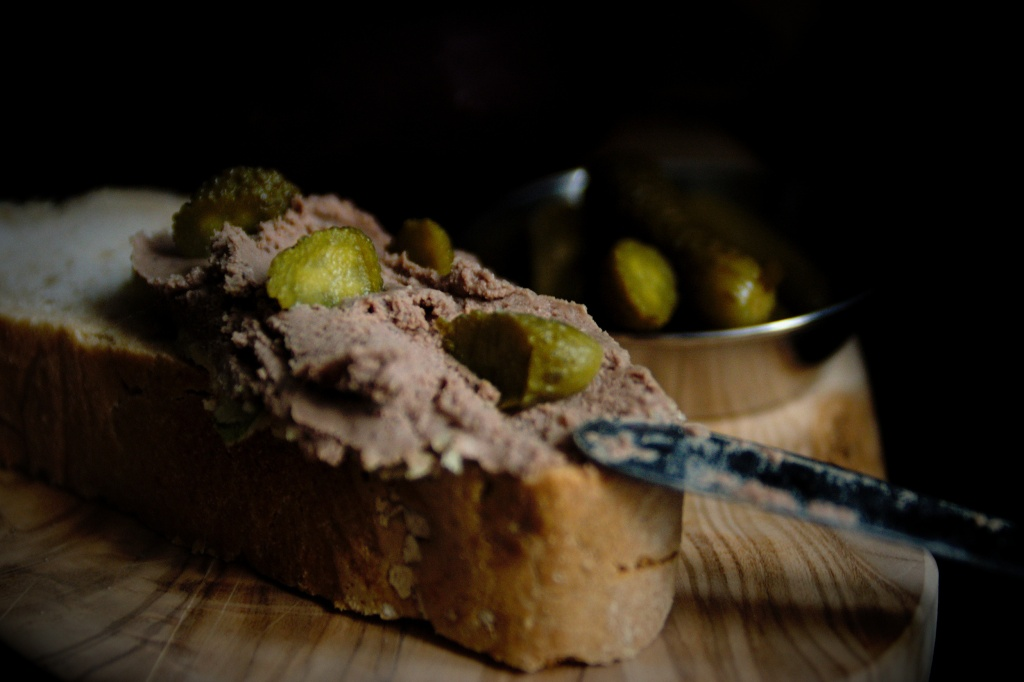 Close up of chicken liver pâté being spread on sourdough bread