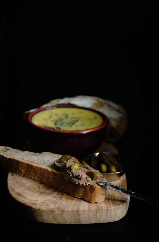 Side view of chicken liver pâté with sourdough bread and cornichons