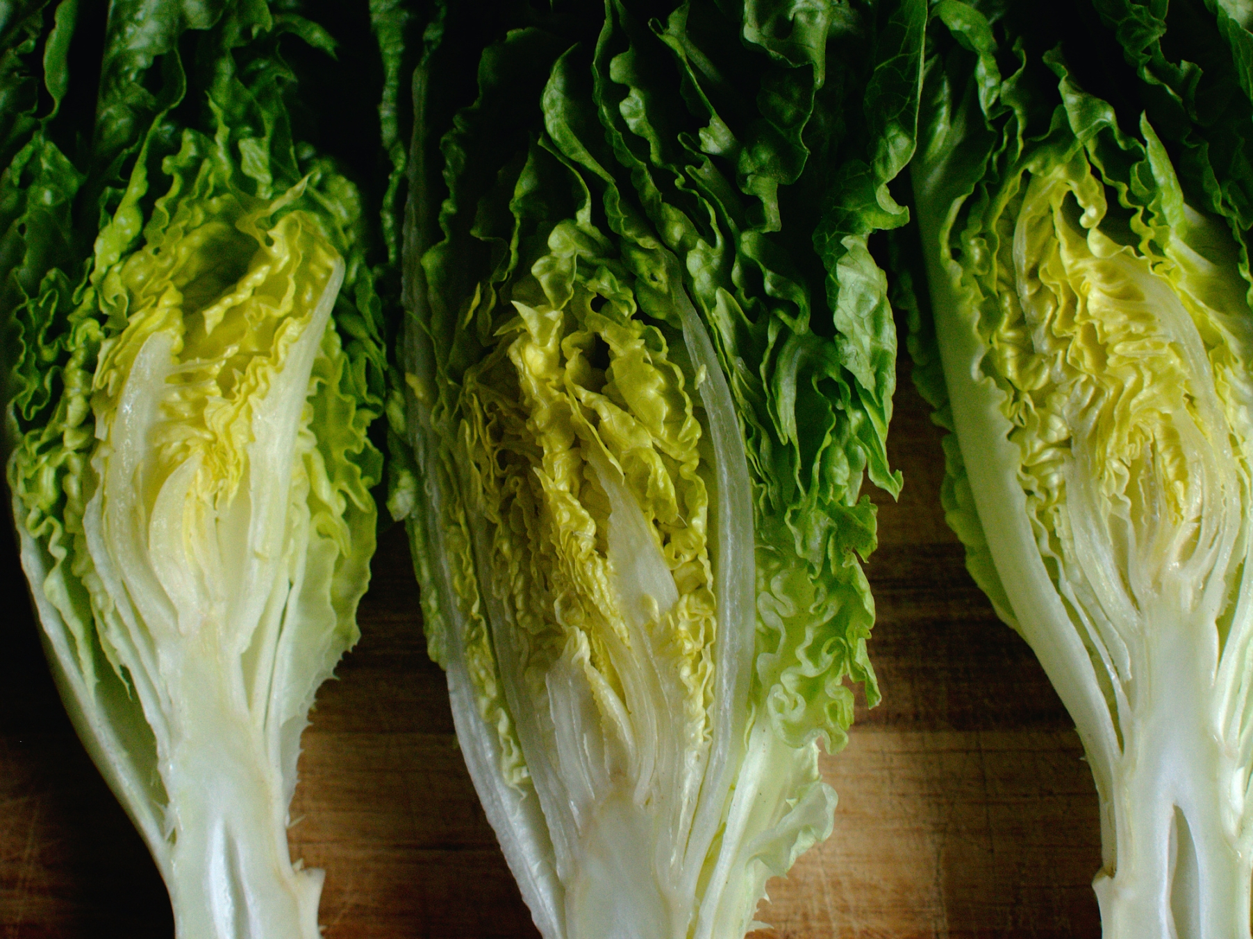 Close up of lettuce halves on a wooden chopping board