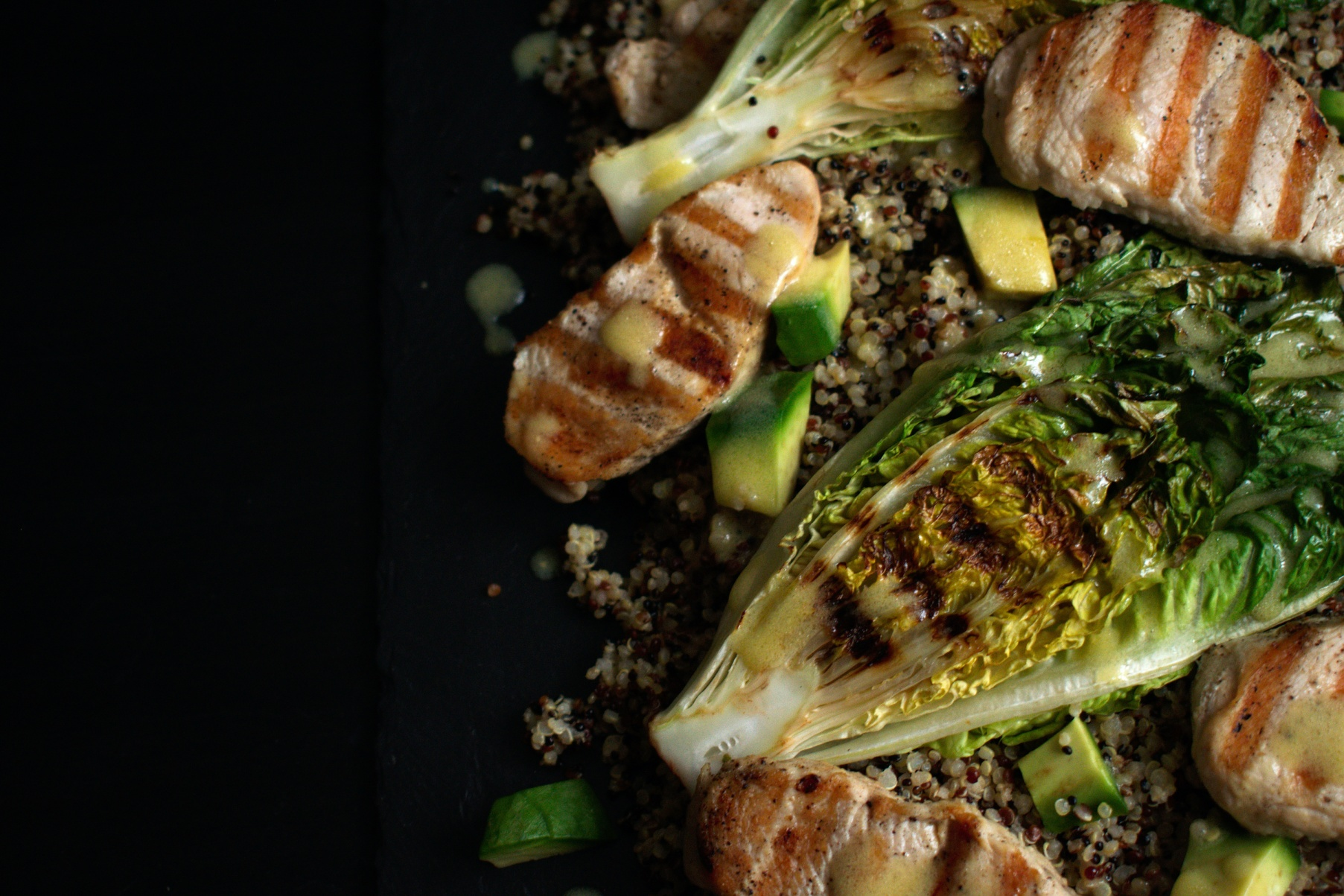 Close up of turkey, quinoa and charred lettuce salad with a lemon mustard dressing