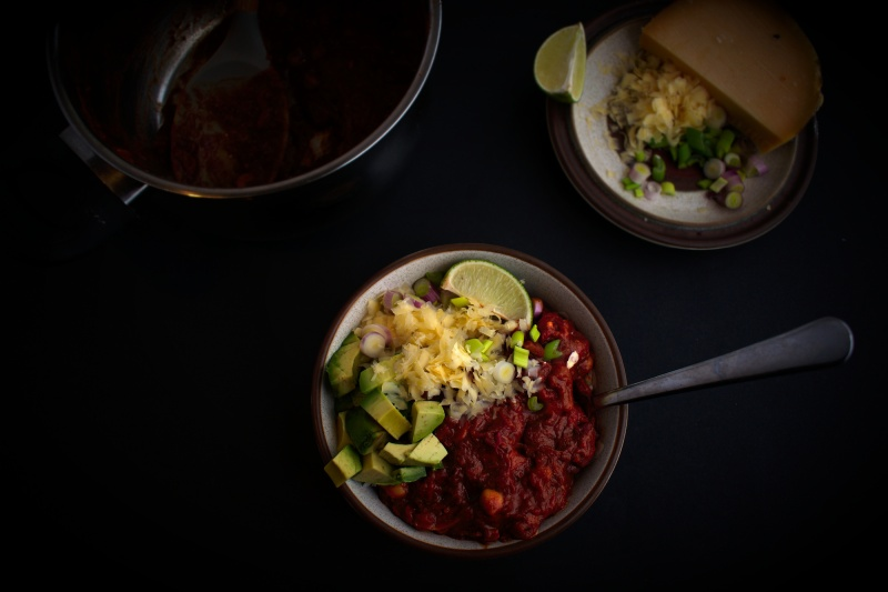 Bowl of chilli con carne with avocado, grated cheese, spring onions and a wedge of lime